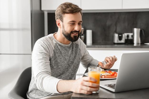 Uśmiechnięty dorosły mężczyzna lat 30. ubrany w zwykłe ubranie, jedzenie jajecznicy na śniadanie i picie soku w domu podczas korzystania z laptopa