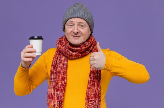 Uśmiechnięty dorosły mężczyzna w czapce zimowej i szaliku na szyi, trzymający papierowy kubek i trzymający kciuki w górę
