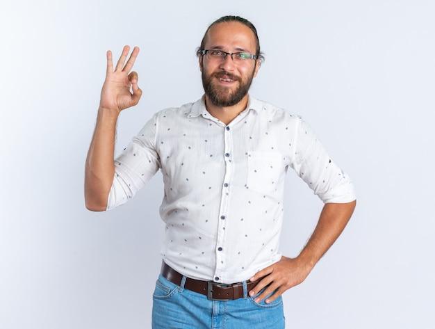 Uśmiechnięty dorosły przystojny mężczyzna w okularach trzymający rękę w talii, patrzący na kamerę robi ok znak na białej ścianie
