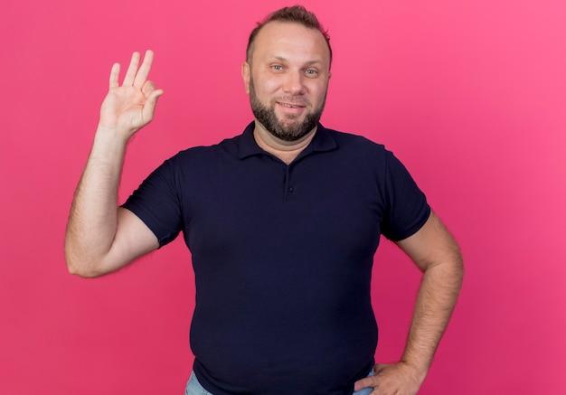 Uśmiechnięty dorosły słowiański mężczyzna kładzie rękę na talii i robi ok znak na białym tle na różowej ścianie