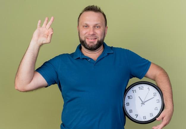 Uśmiechnięty dorosły słowiański mężczyzna trzyma zegar i robi ok znak