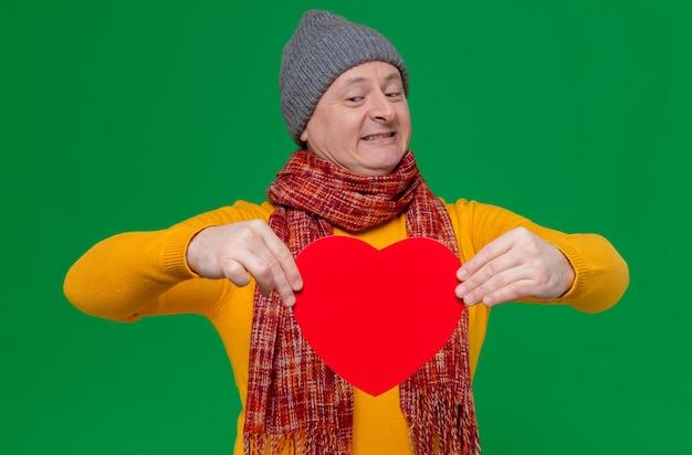 Uśmiechnięty dorosły słowiański mężczyzna w czapce zimowej i szaliku na szyi, trzymający i patrzący na kształt czerwonego serca