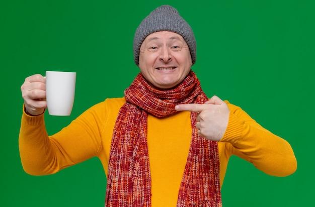 Uśmiechnięty dorosły słowiański mężczyzna w czapce zimowej i szaliku na szyi, trzymający i wskazujący na filiżankę