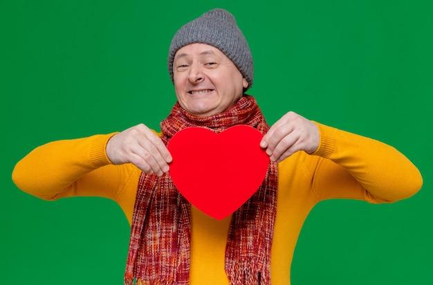 Uśmiechnięty dorosły słowiański mężczyzna w czapce zimowej i szaliku na szyi, trzymający kształt czerwonego serca i