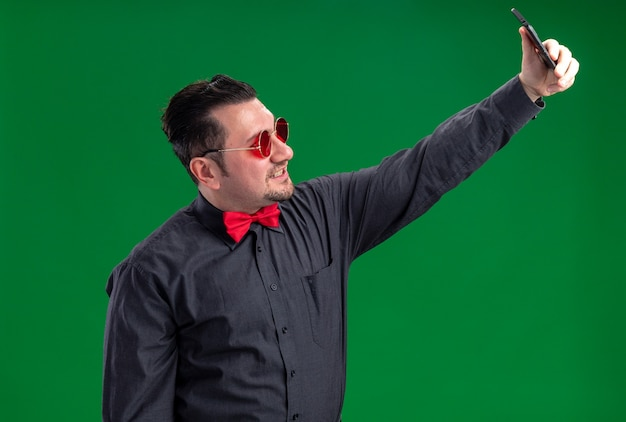 Uśmiechnięty dorosły słowiański mężczyzna w czerwonych okularach przeciwsłonecznych biorący selfie na telefon
