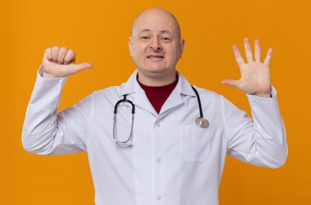 Uśmiechnięty dorosły słowiański mężczyzna w mundurze lekarza ze stetoskopem wskazującym sześć palcami