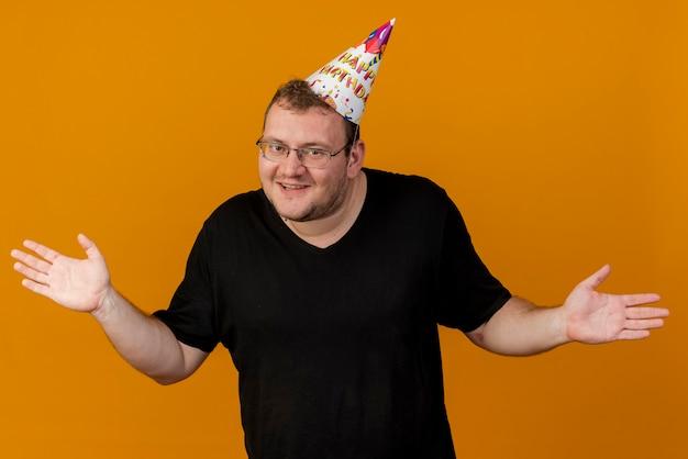 Uśmiechnięty dorosły słowiański mężczyzna w okularach optycznych w czapce urodzinowej stoi trzymając ręce otwarte