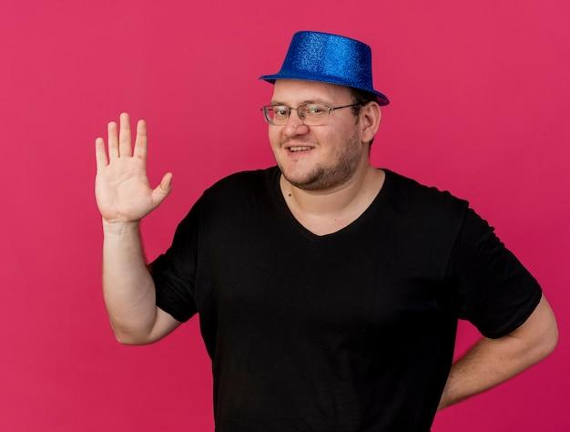 Uśmiechnięty dorosły słowiański mężczyzna w okularach optycznych w niebieskiej imprezowej czapce stoi z podniesioną ręką