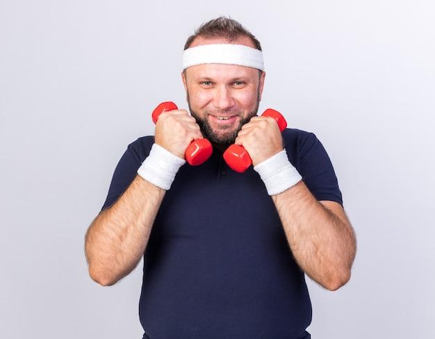 Uśmiechnięty dorosły słowiański sportowy mężczyzna noszący opaskę i opaski na nadgarstki trzymający hantle izolowane na białej ścianie z kopią przestrzeni