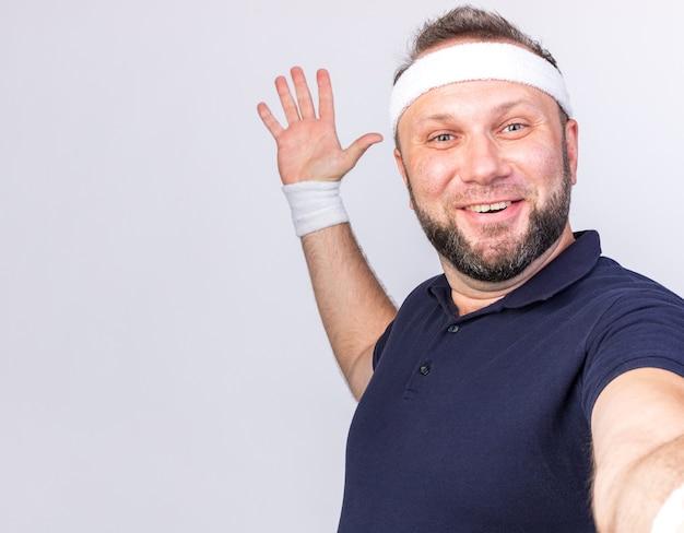 Uśmiechnięty dorosły słowiański sportowy mężczyzna noszący opaskę i opaski stojące z podniesioną ręką, udając, że robi selfie na białym tle na białej ścianie z miejscem na kopię