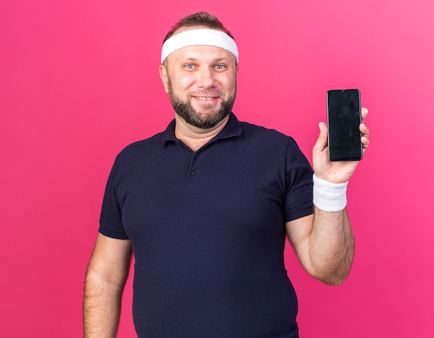 Uśmiechnięty dorosły słowiański sportowy mężczyzna ubrany w opaskę i opaski na rękę trzymając telefon na białym tle na różowej ścianie z miejsca na kopię