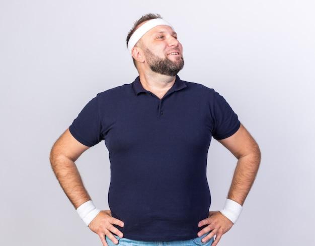 Uśmiechnięty dorosły słowiański sportowy mężczyzna w opasce i opaskach na rękę kładzie ręce na talii i patrzy w bok odizolowany na białej ścianie z miejscem na kopię