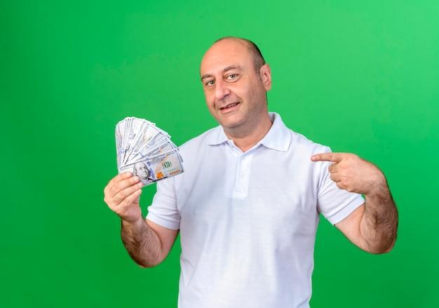 Uśmiechnięty dorywczo dojrzały mężczyzna trzyma i wskazuje na gotówkę na białym tle na zielonej ścianie