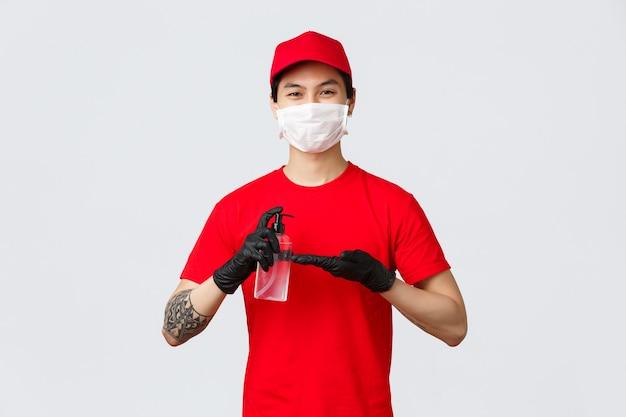 Uśmiechnięty dostawca w czerwonej czapce i koszulce, załóż maskę medyczną i rękawiczki, zastosuj środek do dezynfekcji rąk, aby chronić przed covid-19, wirusem podczas epidemii. kurier dba o klientów, używa środków dezynfekujących podczas pracy