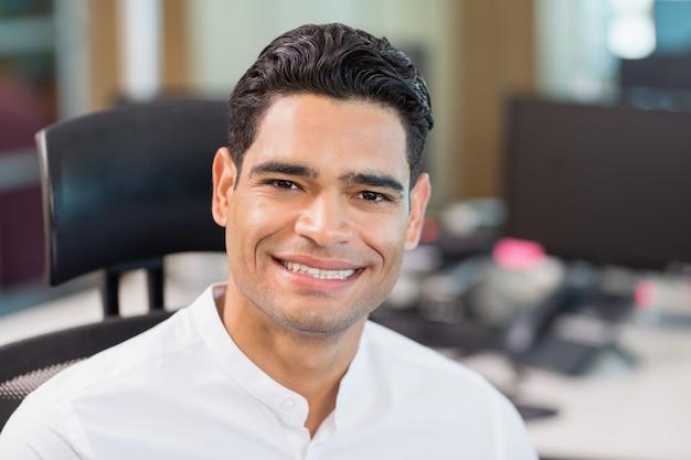 Uśmiechnięty dyrektor wykonawczy siedzi na krześle w biurze