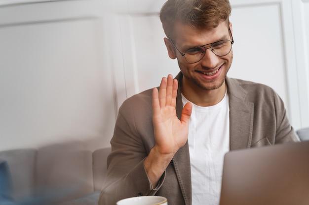 Uśmiechnięty dżentelmen w okularach siedzący przy stole z notatnikiem i machający ręką podczas rozmowy z przyjacielem online w kawiarni