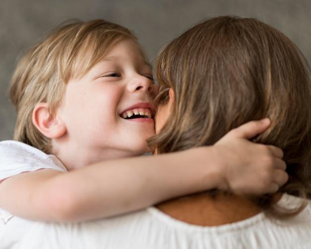 Uśmiechnięty dzieciak przytulający swoją babcię
