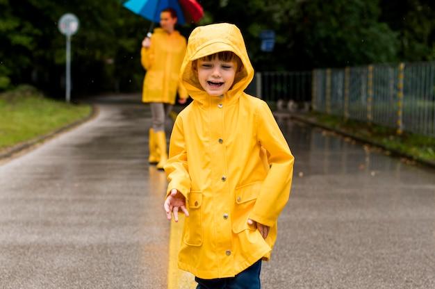 Uśmiechnięty dzieciak w płaszczu przeciwdeszczowym