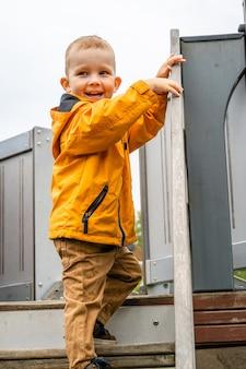 Uśmiechnięty dzieciak z krótkimi włosami wspinający się po schodach
