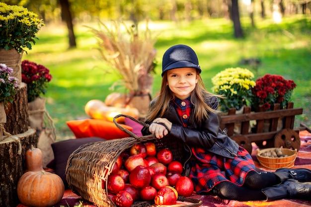 Uśmiechnięty dziecko siedzi w jesień parku z koszem czerwoni jabłka
