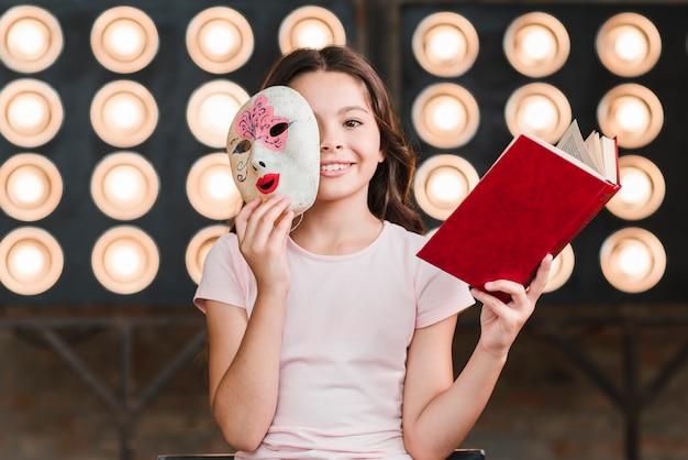 Uśmiechnięty dziewczyny obsiadanie przed sceny światła mienia książką i maską