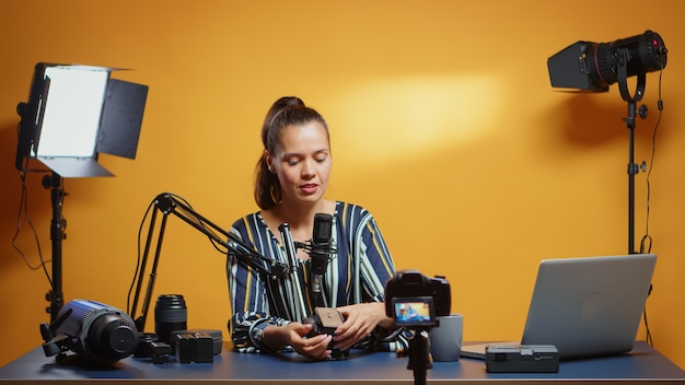 Uśmiechnięty ekspert od filmowania pokazujący przed kamerą sposoby montażu płyty głowicy płynowej. influencer tworzący treści internetowe o sprzęcie wideo dla abonentów i dystrybucji internetowej, cyfrowe rozmowy vlogowe