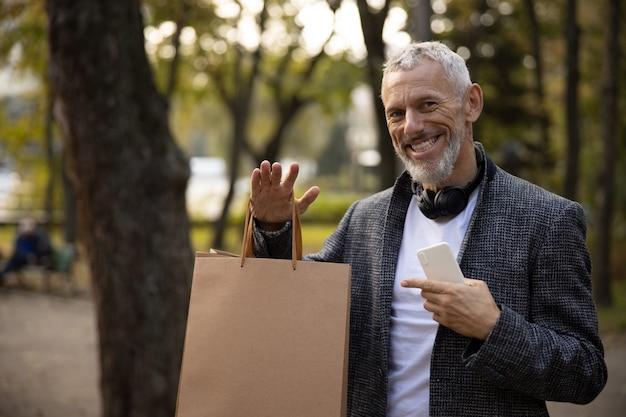 Uśmiechnięty elegancki mężczyzna z zakupami i smartfonem