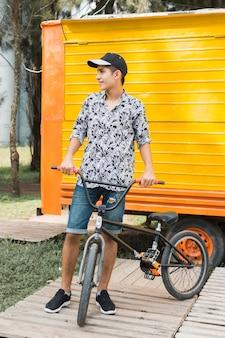 Uśmiechnięty elegancki nastoletni chłopak patrzeje daleko od z jego bicyklem