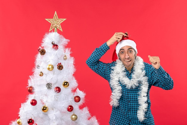 Uśmiechnięty emocjonalny zabawny młody człowiek z czapką świętego mikołaja w niebieskiej koszuli w paski