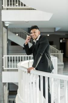 Uśmiechnięty etniczny kierownika odpowiadania rozmowa telefonicza na balkonie