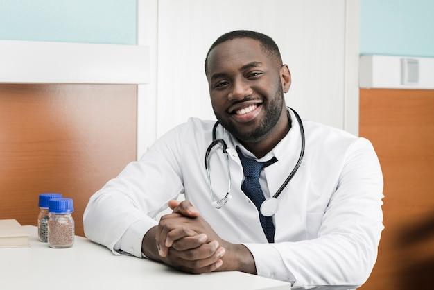Uśmiechnięty etniczny student medycyny przy stołem