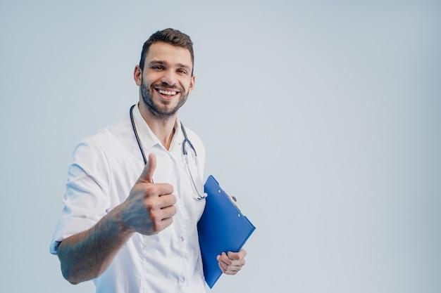 Uśmiechnięty europejski mężczyzna lekarz z stetoskopem i schowkiem. młody brodaty mężczyzna ubrany w biały płaszcz pokazując kciuk do góry gest. na białym tle na szarym tle z turkusowym światłem. sesja studyjna. skopiuj miejsce.