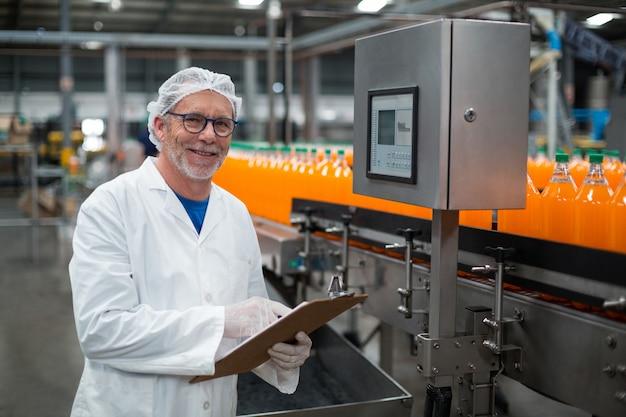 Uśmiechnięty fabryczny inżynier utrzymuje rejestr na schowku w fabryce