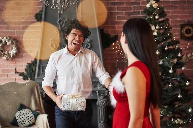 Uśmiechnięty facet idzie do dziewczyny. kobieta w czerwonej sukience otrzyma teraz prezent świąteczny od chłopaka.