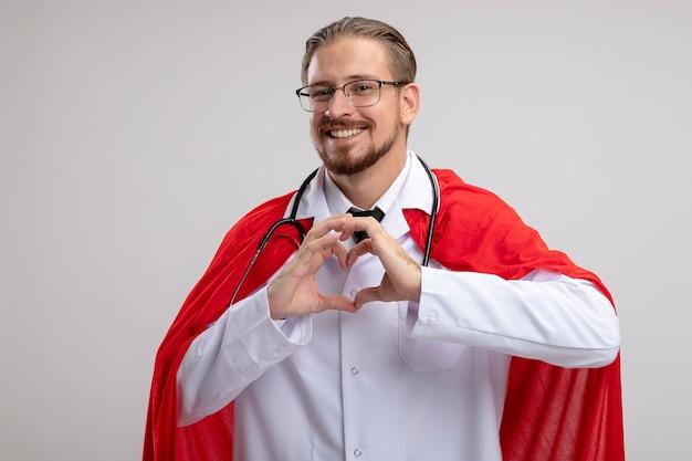Uśmiechnięty facet młody superbohater na sobie szlafrok medyczny ze stetoskopem i okularami pokazując gest serca na białym tle