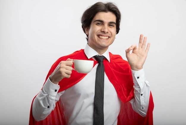 Uśmiechnięty facet młody superbohater patrząc na kamery na sobie krawat trzymając filiżankę kawy