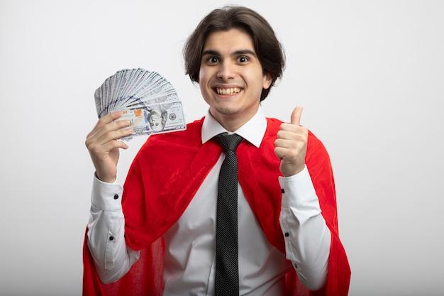 Uśmiechnięty facet młody superbohater sobie krawat trzyma gotówkę i pokazuje kciuk na białym tle