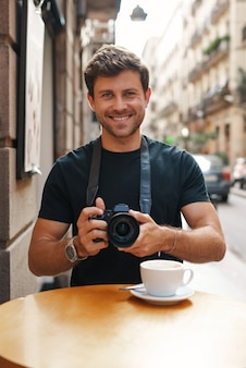 Uśmiechnięty facet robi zdjęcia aparatem fotograficznym w ulicznej kawiarni