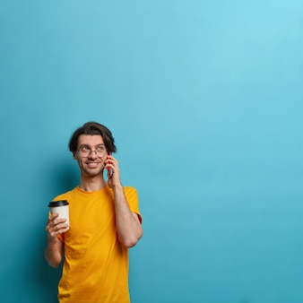 Uśmiechnięty facet trzyma komórkę blisko ucha, zajęty rozmową z przyjacielem, omawia dobre wieści, trzyma filiżankę kawy na wynos, komunikuje się przyjemnie, pozuje na niebieskim tle, kopiuje miejsce na informacje
