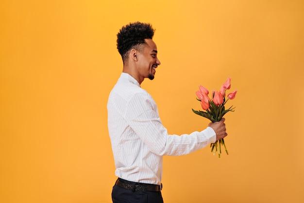 Uśmiechnięty facet w białej koszuli trzyma różowe tulipany