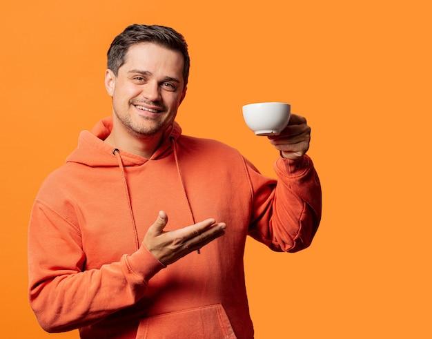 Uśmiechnięty facet w pomarańczowej bluzie z kapturem z filiżanką na pomarańczowo