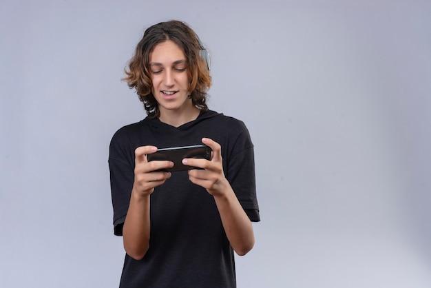 Uśmiechnięty facet z długimi włosami w czarnej koszulce gra z telefonu na białej ścianie