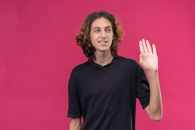 Uśmiechnięty facet z długimi włosami w czarnej koszulce pokazuje cześć ręką na różowej ścianie