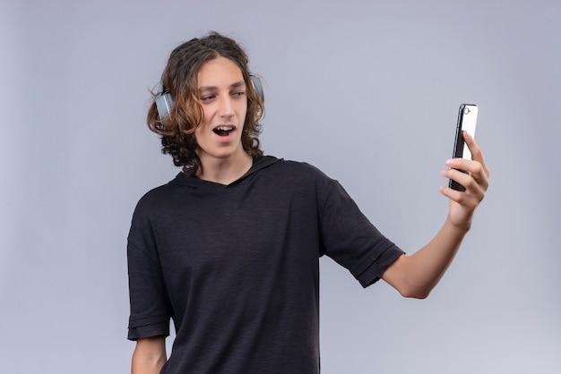 Uśmiechnięty facet z długimi włosami w czarnej koszulce w słuchawkach i weź selfie na białej ścianie