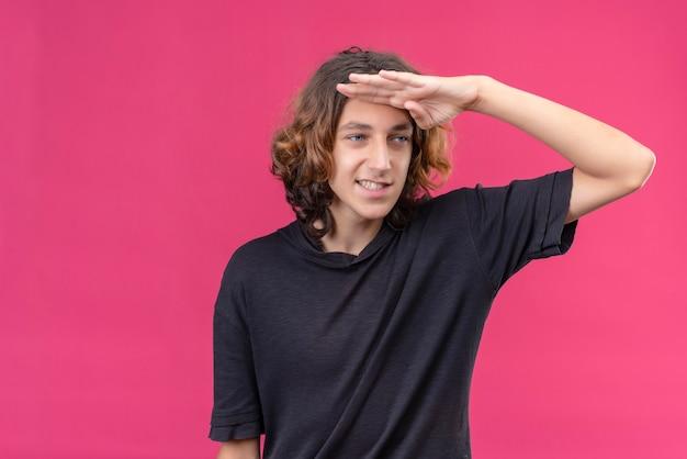 Uśmiechnięty facet z długimi włosami w czarnej koszulce wyglądają na odległość z ręką na różowej ścianie