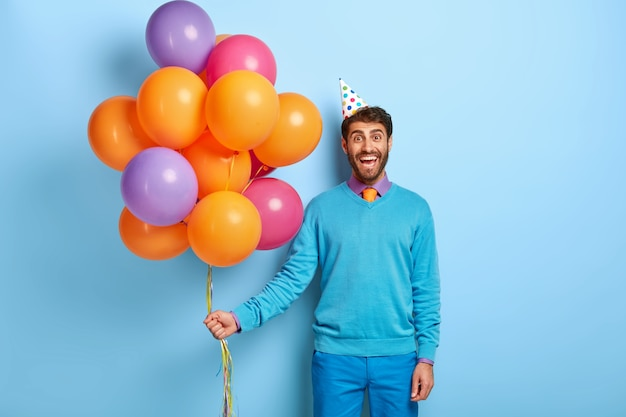 Uśmiechnięty facet z urodzinowym kapeluszem i balonami pozuje w niebieskim swetrze