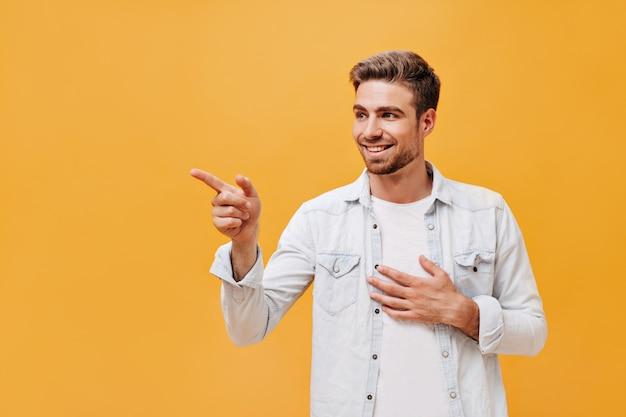 Uśmiechnięty fajny młody człowiek z rudą brodą i brązowymi włosami w stylowych białych ubraniach, odwracający wzrok i pokazujący na bok palec