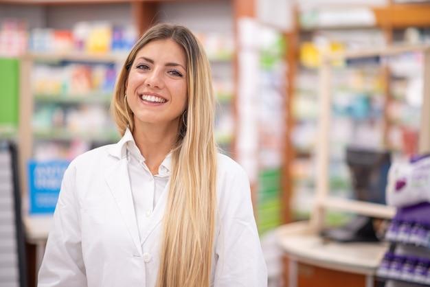 Uśmiechnięty farmaceuta w jej aptece