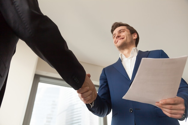 Uśmiechnięty firma kierownik wita klienta w biurze