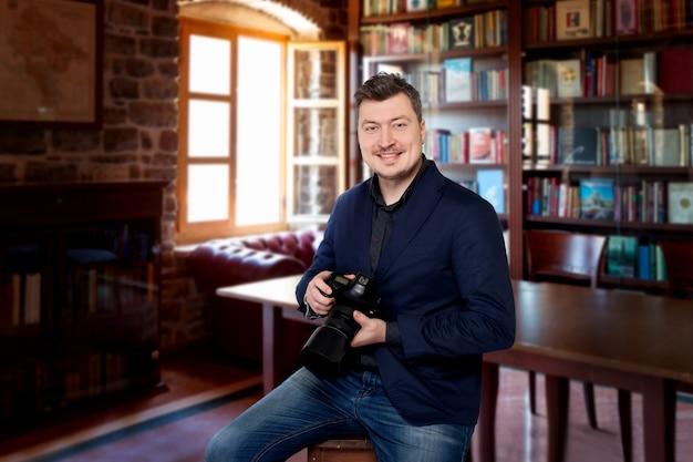 Uśmiechnięty fotograf z aparatem cyfrowym siedzi na krześle, domowa biblioteka